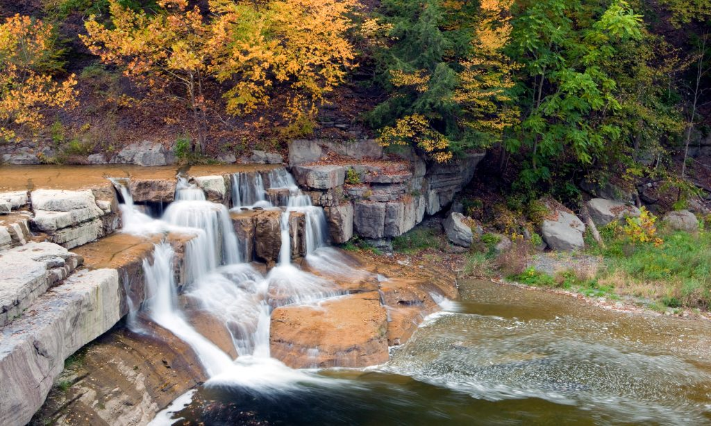 Lower falls at Taughannock Falls State Park in the fall with fall color image for the 5 Best parks in the finger lakes to see fall color for the Gould Hotel in Seneca Falls, New York